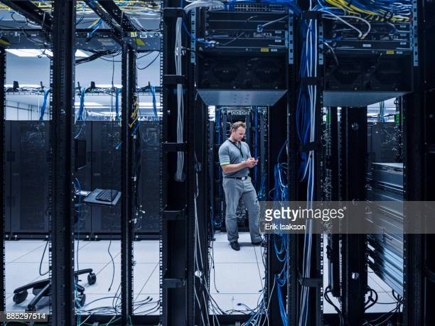 man using mobile phone in server room - data center stock pictures, royalty-free photos & images