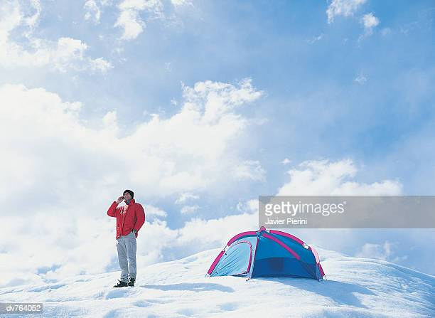 man using mobile phone in snow - snow boot stock photos and pictures
