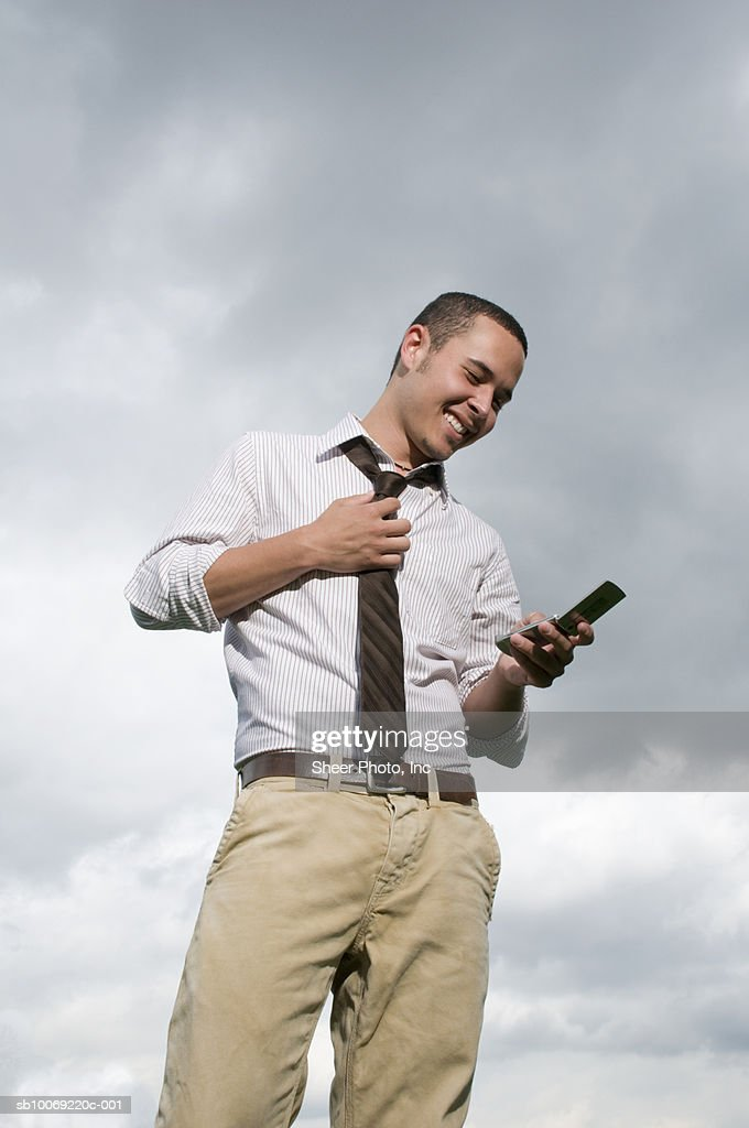 Man using mobile phone, low angle view against sky : Stockfoto