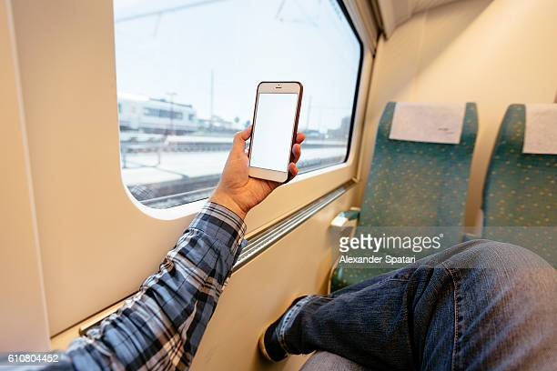 Man using mobile phone on a high speed train, seen from personal perspective