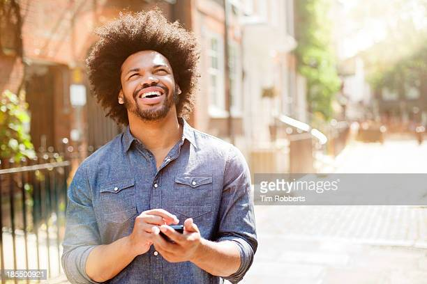 man using mobile phone on street. - satisfaction stock pictures, royalty-free photos & images