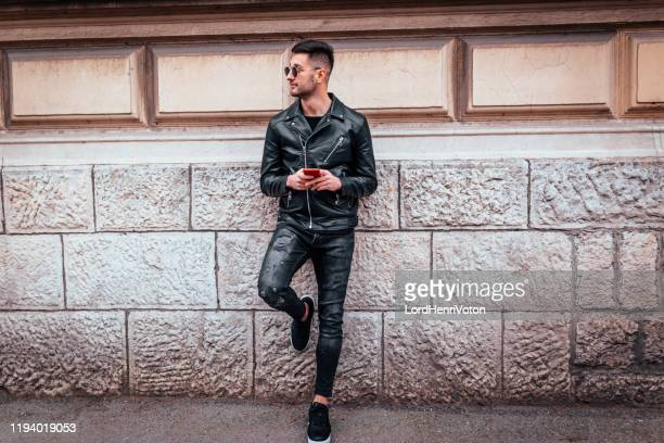 man using mobile phone outdoor - biker jacket stock pictures, royalty-free photos & images
