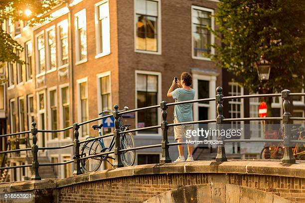 man using mobile phone to photograph canal - merten snijders stock pictures, royalty-free photos & images