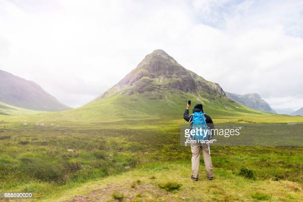 Man using mobile phone to take photo of scenery in Scottish Highlands.