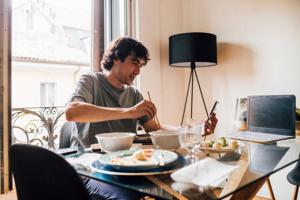 Man using mobile phone while having lunch at home