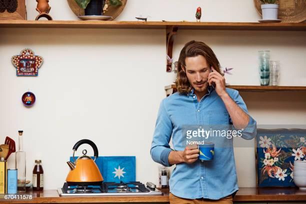 Homme à l'aide de téléphone portable tout en tenant la tasse à café
