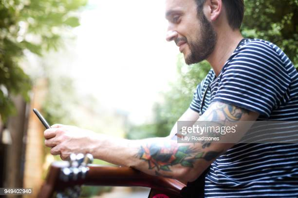 Man using mobile phone while holding guitar