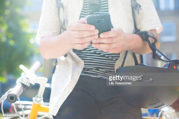 Man using mobile phone while leaning on bicycle