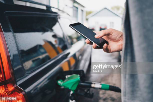 Man using mobile phone while refueling car at gas station