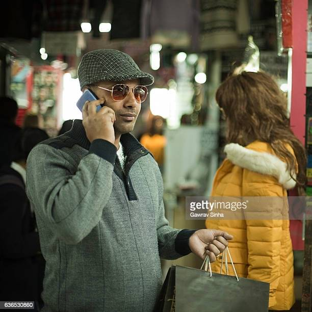 Man using mobile phone while shopping in the market.