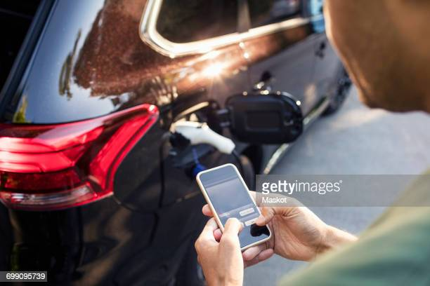 Man using mobile phone while standing by charging electric car