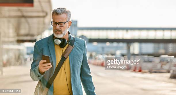 man using mobile phone while walking on sidewalk - gray coat stock pictures, royalty-free photos & images