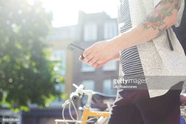 Man using mobile phone while walking past bicycle