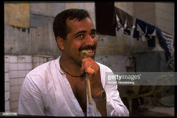 Man using new neem stick toothbrush