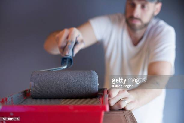 Man using paint roller to paint the walls with gray color