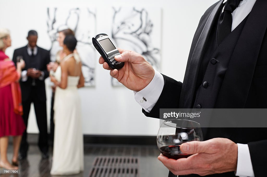 Man Using PDA at Art Gallery : Stock Photo