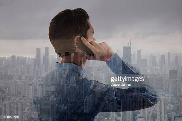 man using phone and cityscape