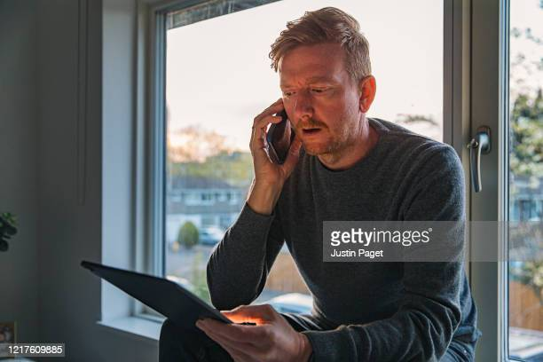 man using phone and digital tablet on window sill - talking stock pictures, royalty-free photos & images