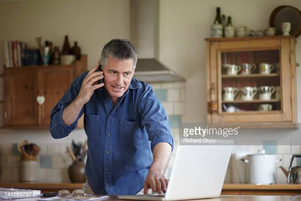 man using phone and laptop in kitchen - richard drury stock pictures, royalty-free photos & images
