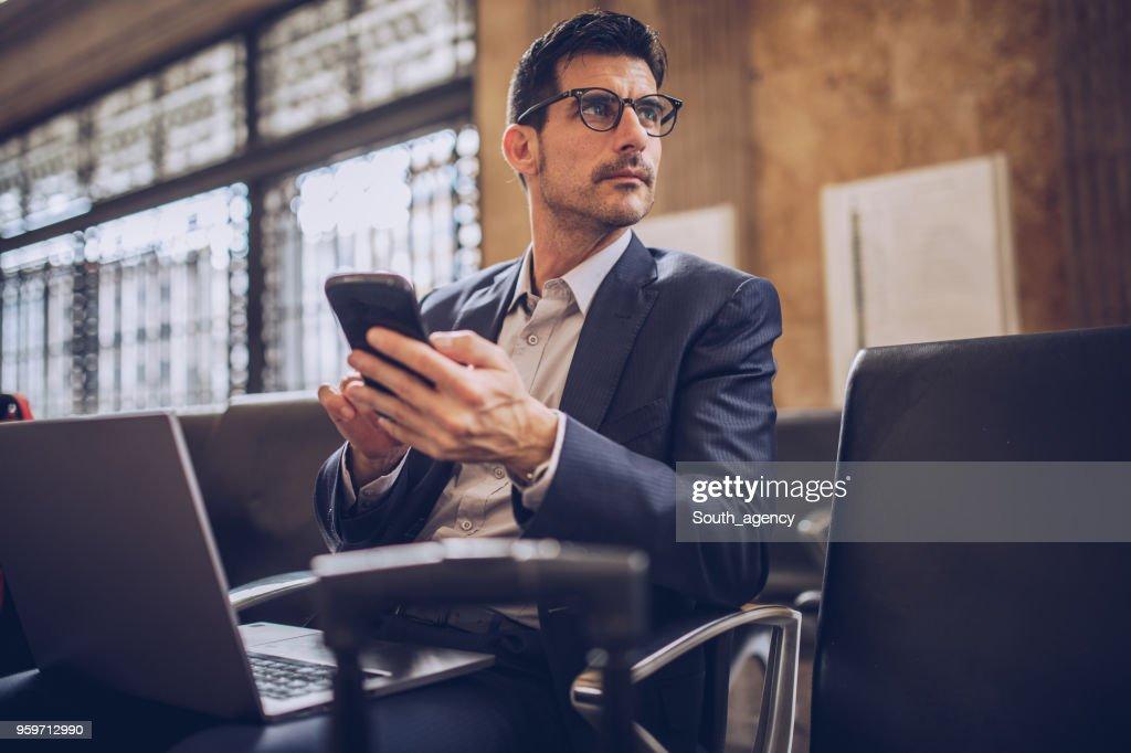 Mann mit Telefon am Bahnhof : Stock-Foto