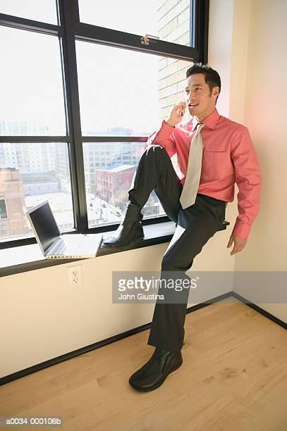 Man Using Phone by Window
