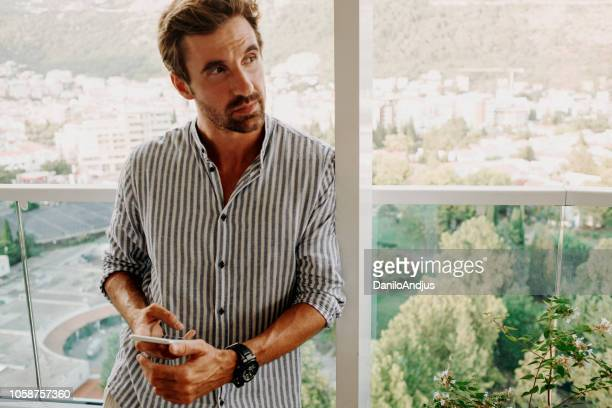 man using phone on the balcony - digital marketing foto e immagini stock