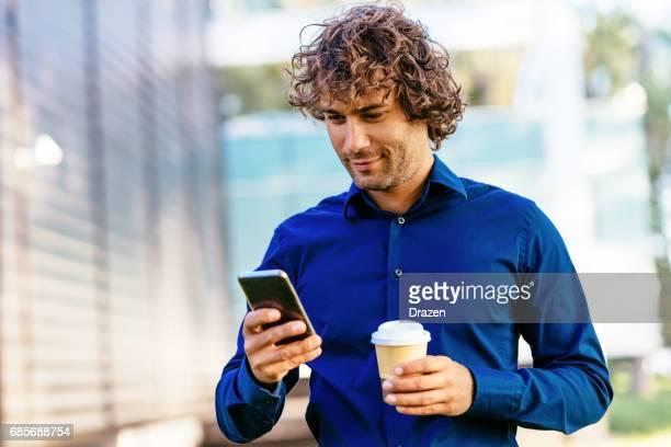 Mann mit Telefon reagieren auf geschäftliche E-mails