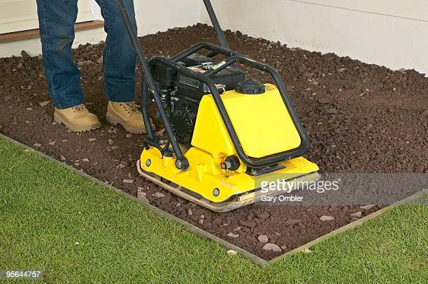 Man using plate compactor on top of hardcore next to grass, close up