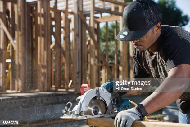 man using power saw to cut wood plank - circular saw stock photos and pictures