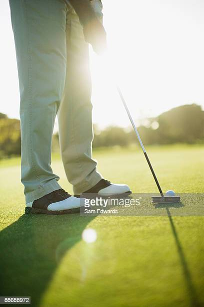 Man using putter to play golf