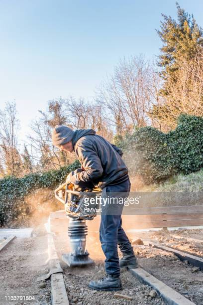 man using rammer tamper (jumping jack) for soil compacting - shaking stock pictures, royalty-free photos & images