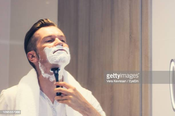man using razor while shaving in bathroom - shaving stock pictures, royalty-free photos & images