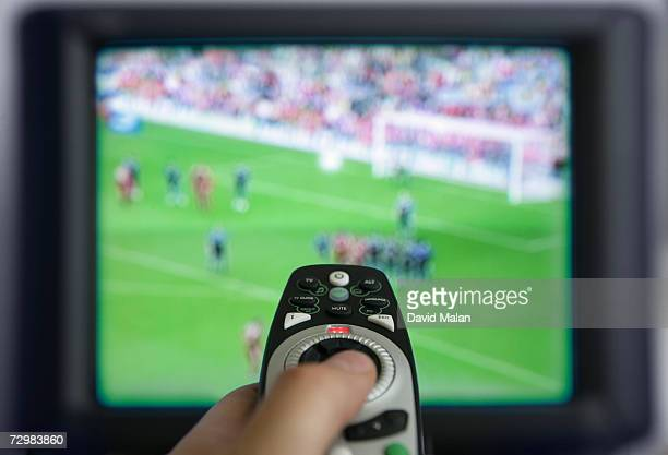 Man using remote control in front of television set, close up on remote,