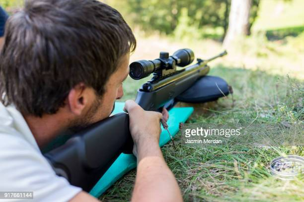 Man using rifle with sniper lying on grass near forest