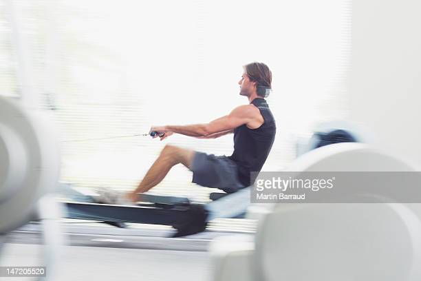 Man using rowing machine in gymnasium