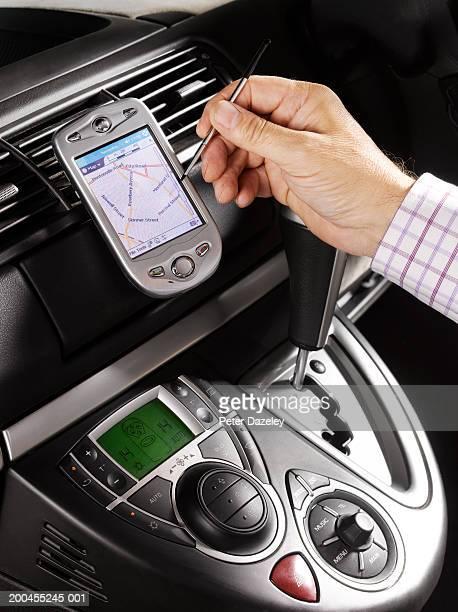 Man using satellite navigation system in car, close-up