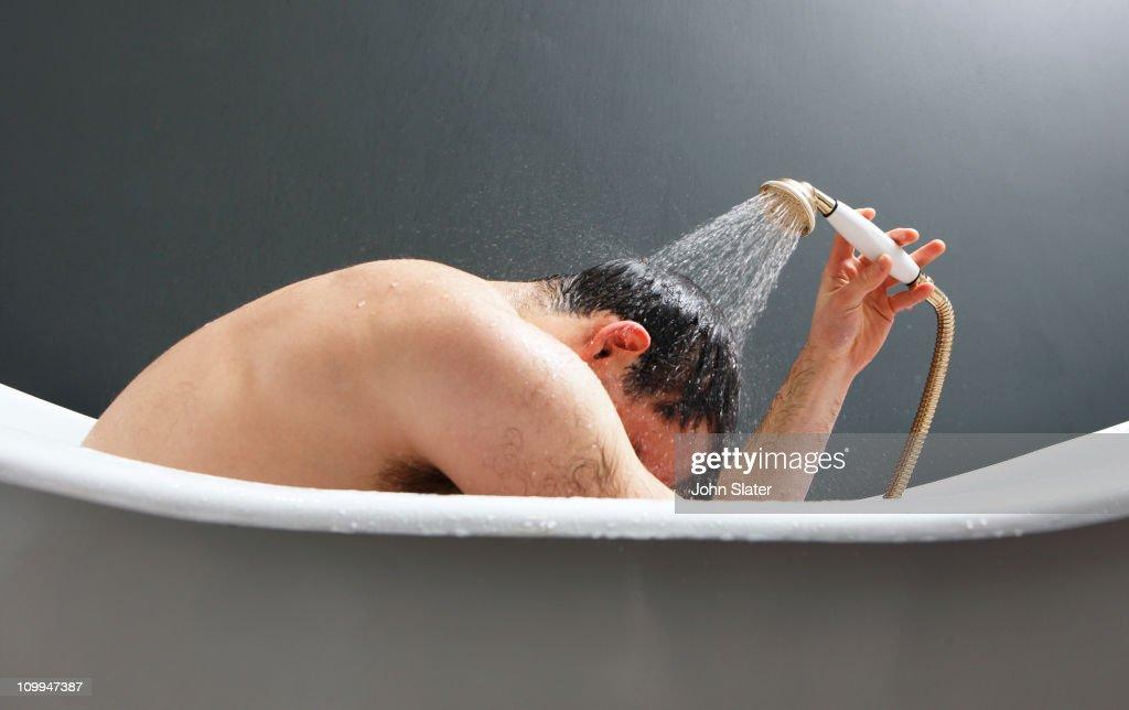man using shower in bath tub : Stock Photo