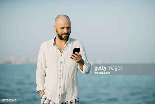 man using smart phone by the sea - nordafrika stock-fotos und bilder