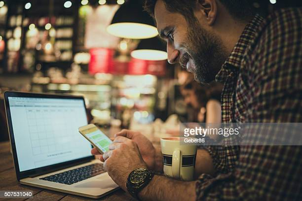 Man using smart phone in cafe