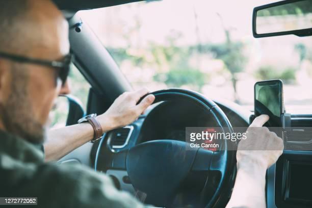 man using smart phone in car - cris cantón photography fotografías e imágenes de stock
