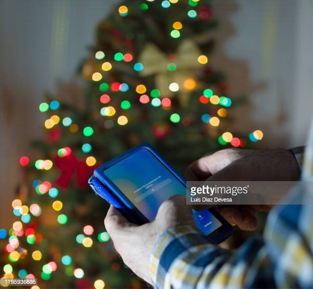 man using smart phone in front of christmas tree - 2020 2029 stock pictures, royalty-free photos & images