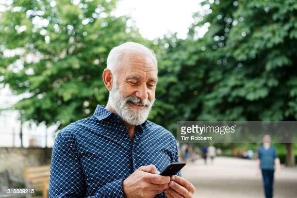 man using smart phone in park - text messaging stock pictures, royalty-free photos & images