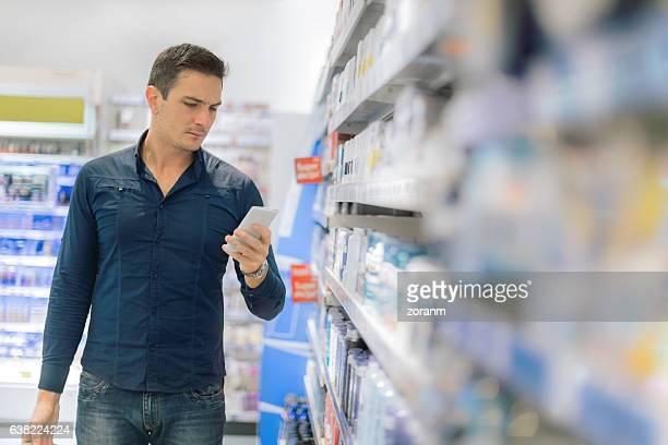 Man using smart phone in supermarket