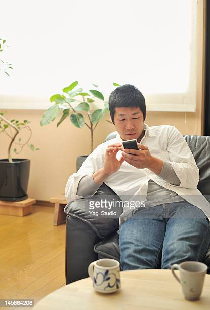 Man using Smart phone in the room.