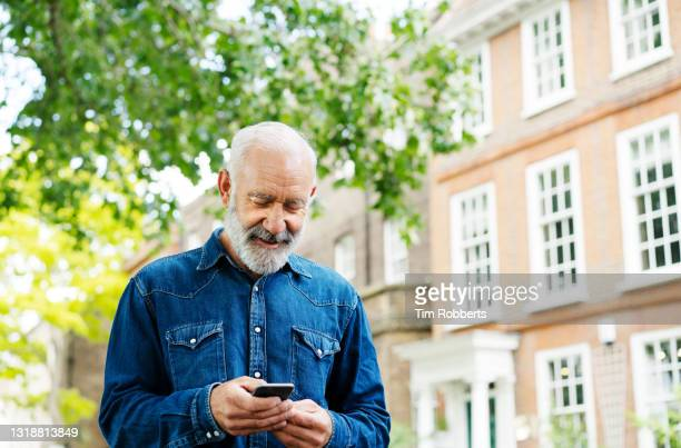 man using smart phone near tree and buildings - only men stock pictures, royalty-free photos & images