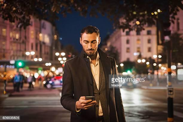Man using smart phone on city street at night