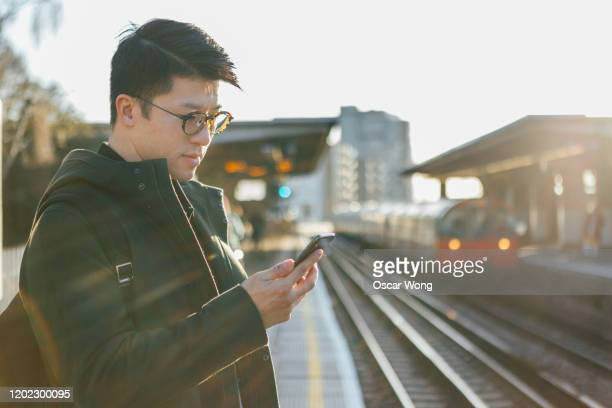 man using smart phone on the platform - vertical red tube fotografías e imágenes de stock