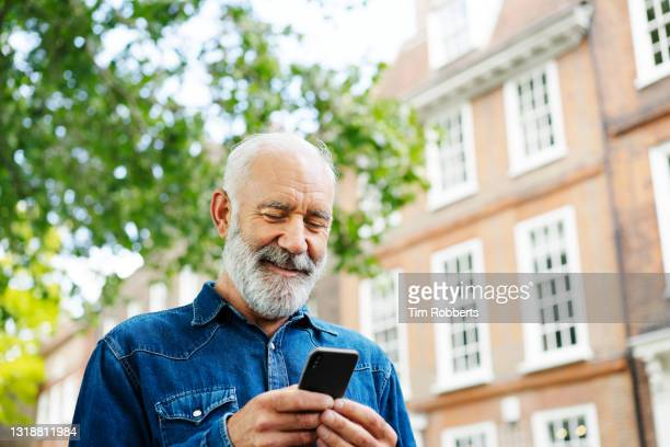 man using smart phone outside - only men stock pictures, royalty-free photos & images
