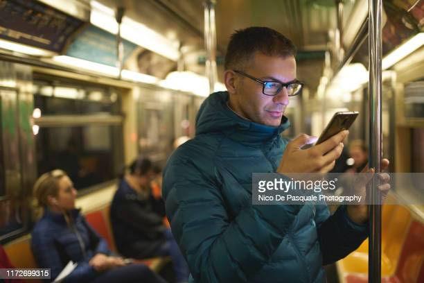 man using smart phone - subway train stock pictures, royalty-free photos & images