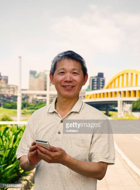 Man using smart phone, smiling looking at camera, Taipei.